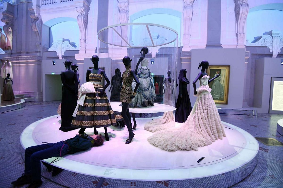 A man adjusts a dress prior tot the opening of the Dior exhibition that celebrates the seventieth anniversary of the Christian Dior fashion house on July 3, 2017 in Paris.The exhibition at the Museum of Decorative Arts (Musee des Arts Decoratifs) is