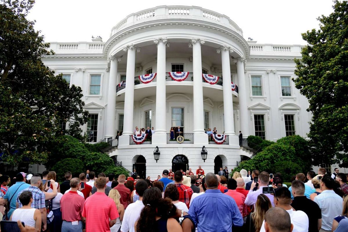 President Donald Trump and First Lady Melania Trump (centre), along with Vice President Mike Pence and his wife Karen welcome military families who have gathered for a Fourth of July picnic on the South Lawn of the White House, prior to a fireworks d