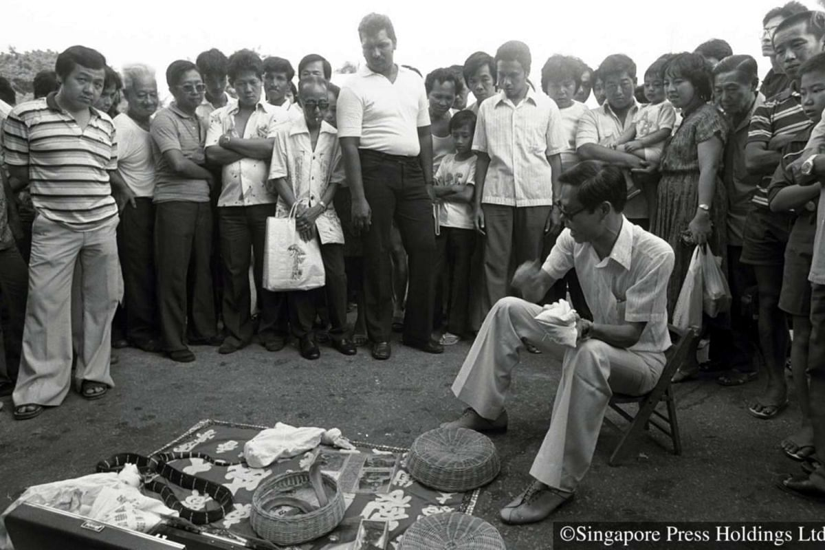 1982: A Chinese medicine man pulling in the crowds as he espouses the medicinal value of snakes as a cure for various conditions.