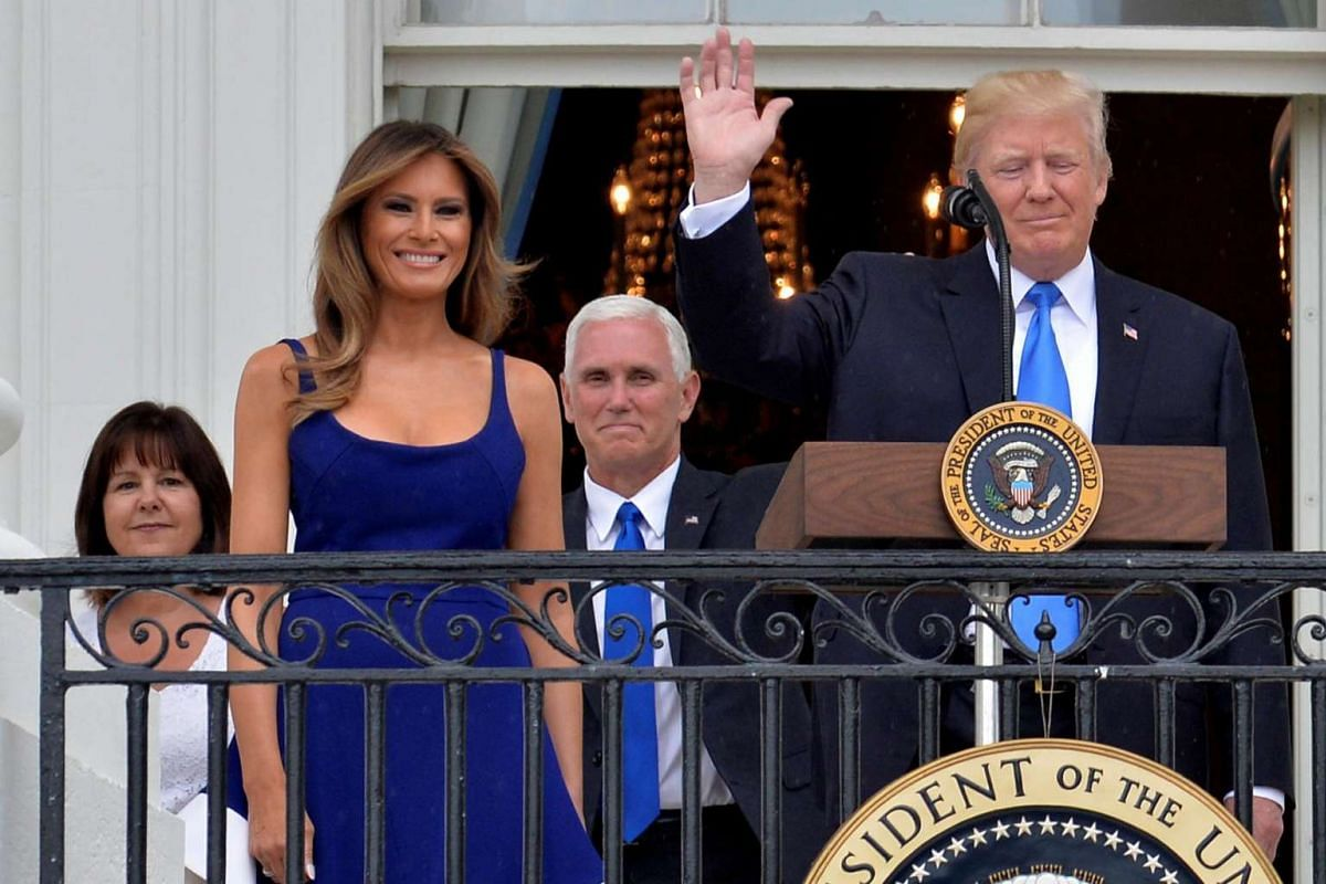 President Donald Trump (right) and First Lady Melania Trump (second, left) arrive along with Vice President Mike Pence (centre, background) and his wife Karen, to welcome military families who have gathered for a Fourth of July picnic.