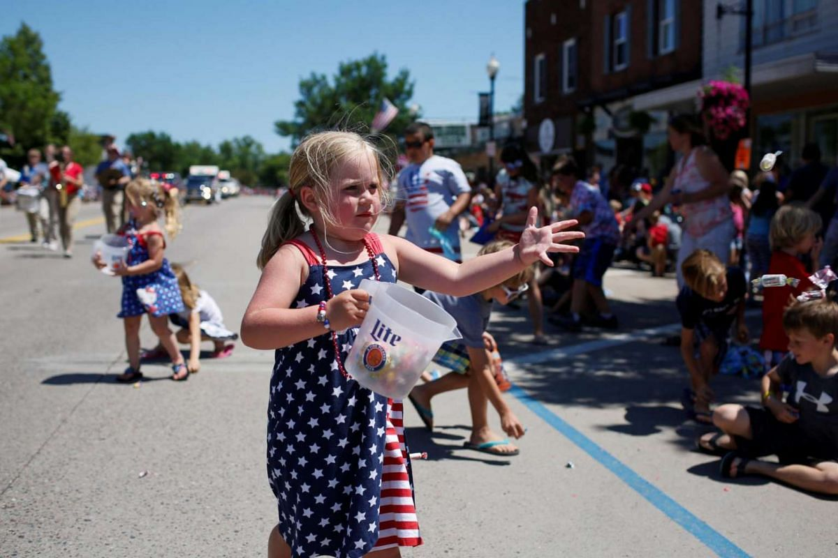 A girl throws candy to those on the sidelines of the 'Pow Wow Days Parade' during Independence Day celebrations in Tomahawk, Wisconsin, US, on July 4, 2017.