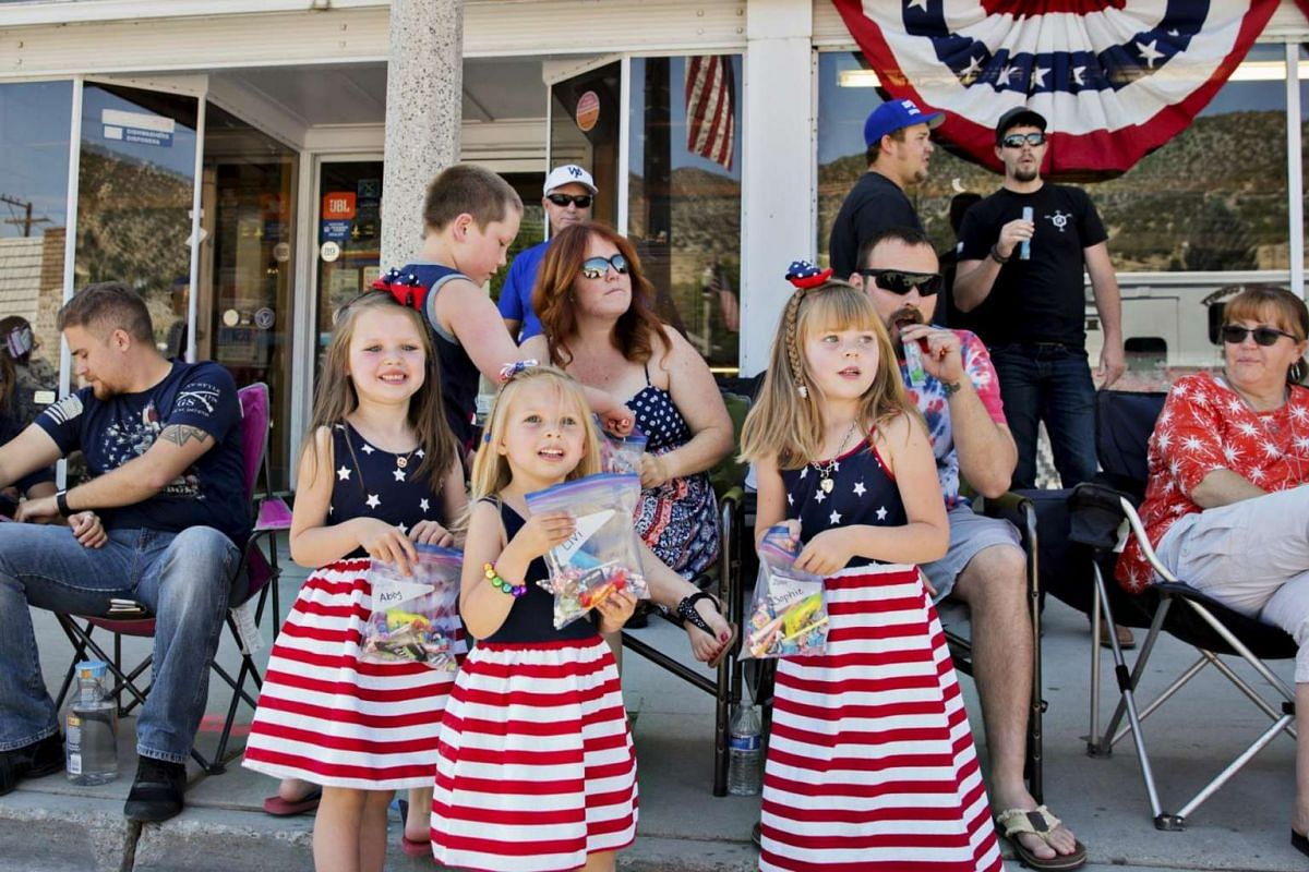 Children in festive dresses watch the Fourth of July parade in  Ely, Nevada,  on  4 July, 2017.