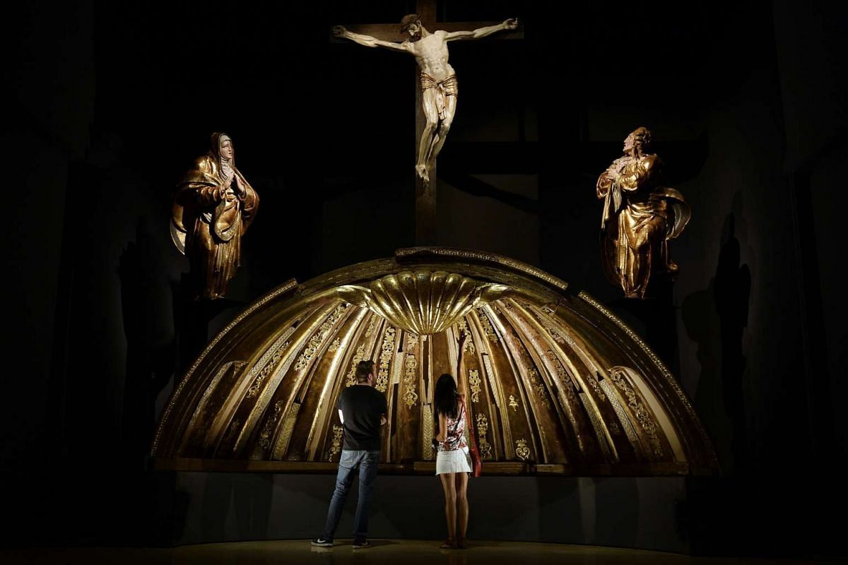 Visitors observe the scallop shell of San Benito el Real high altarpiece dome, by Spanish sculptor Alonso Berruguete, as part of the exhibition 'Laocoon and His Sons. Alonso de Berruguete and Pagan Age', at the national Museum of Sculpture, in Vallad