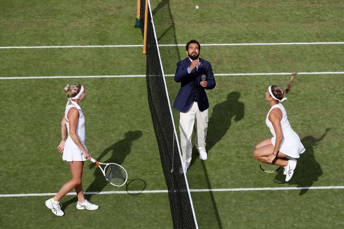 The umpire tosses the coin before the start of the Wimbledon match between Puerto Rico's Monica Puig and Switzerland's Timea Bacsinszky in London on July 4, 2017.