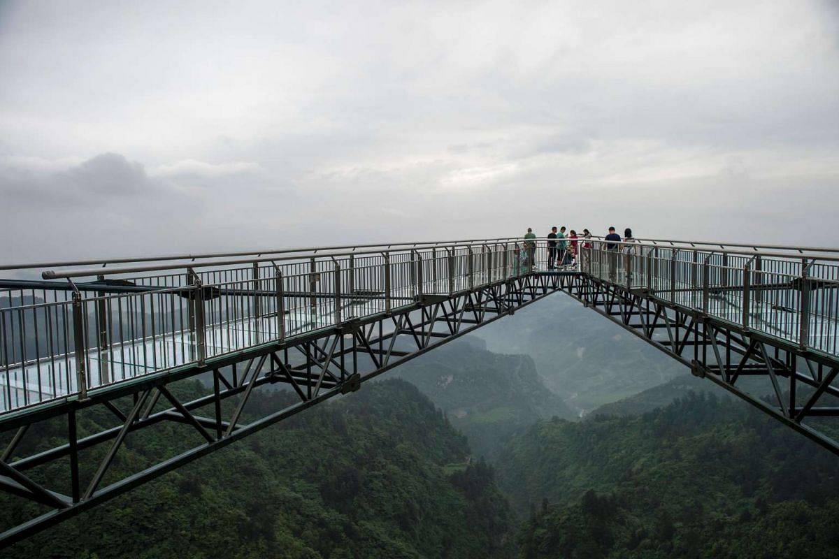 Tourists look on from a glass-bottomed skywalk, certified as the world's longest, at the Ordovician park in Wansheng. Hovering more than 100 metres above a gaping chasm, a glass-bottomed skywalk has set a record in China while delighting and terrifyi