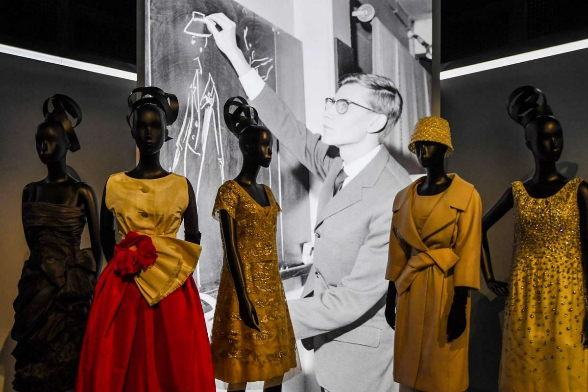 Dresses by French fashion designer Yves Saint Laurent (whose picture is seen behind) in the Dior exhibition that celebrates the 70th anniversary of the Christian Dior fashion house on July 3, 2017 in Paris.