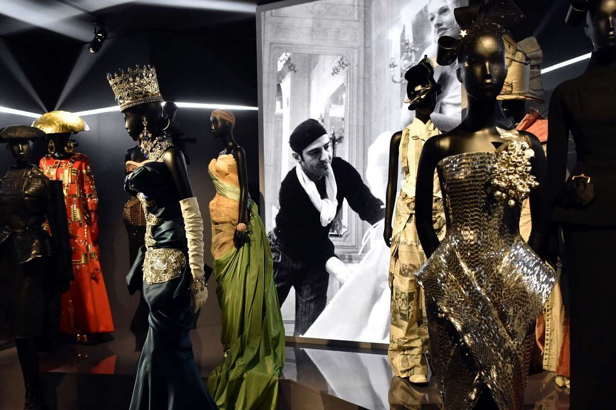 Dresses by British fashion designer John Galliano (whose picture is seen behind) in the Dior exhibition that celebrates the 70th anniversary of the Christian Dior fashion house on July 3, 2017 in Paris.