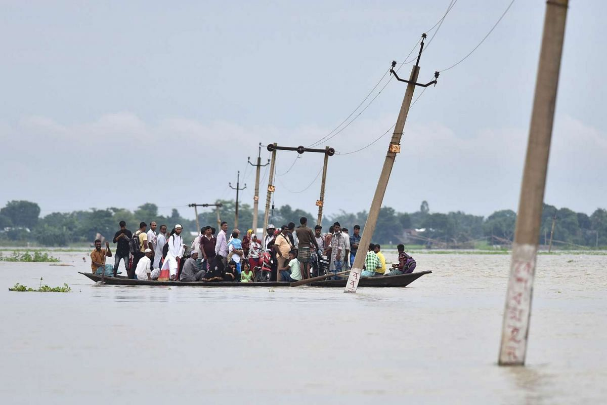 Indian villagers travel by boat through floodwaters in Balimukh Ashigarh village in Morigoan district, in India's northeastern state of Assam, on July 4, 2017. Floods have affected 350,000 people living across 13 districts in Assam as the annual mons