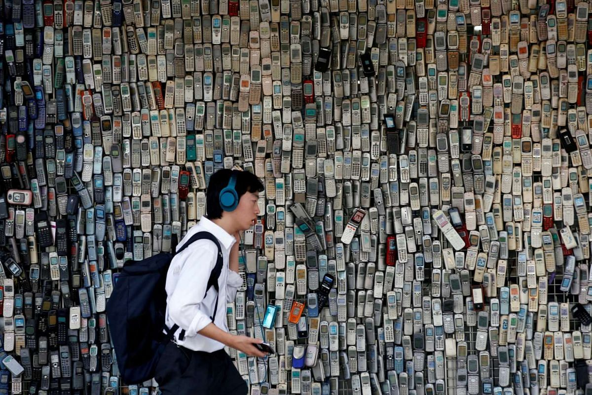 A man using a smartphone walks past an electronic shop's wall decorated with old cell phones which its owner Watanabe Masanao had collected over 20 years is pictured in Tokyo, Japan July 5, 2017.