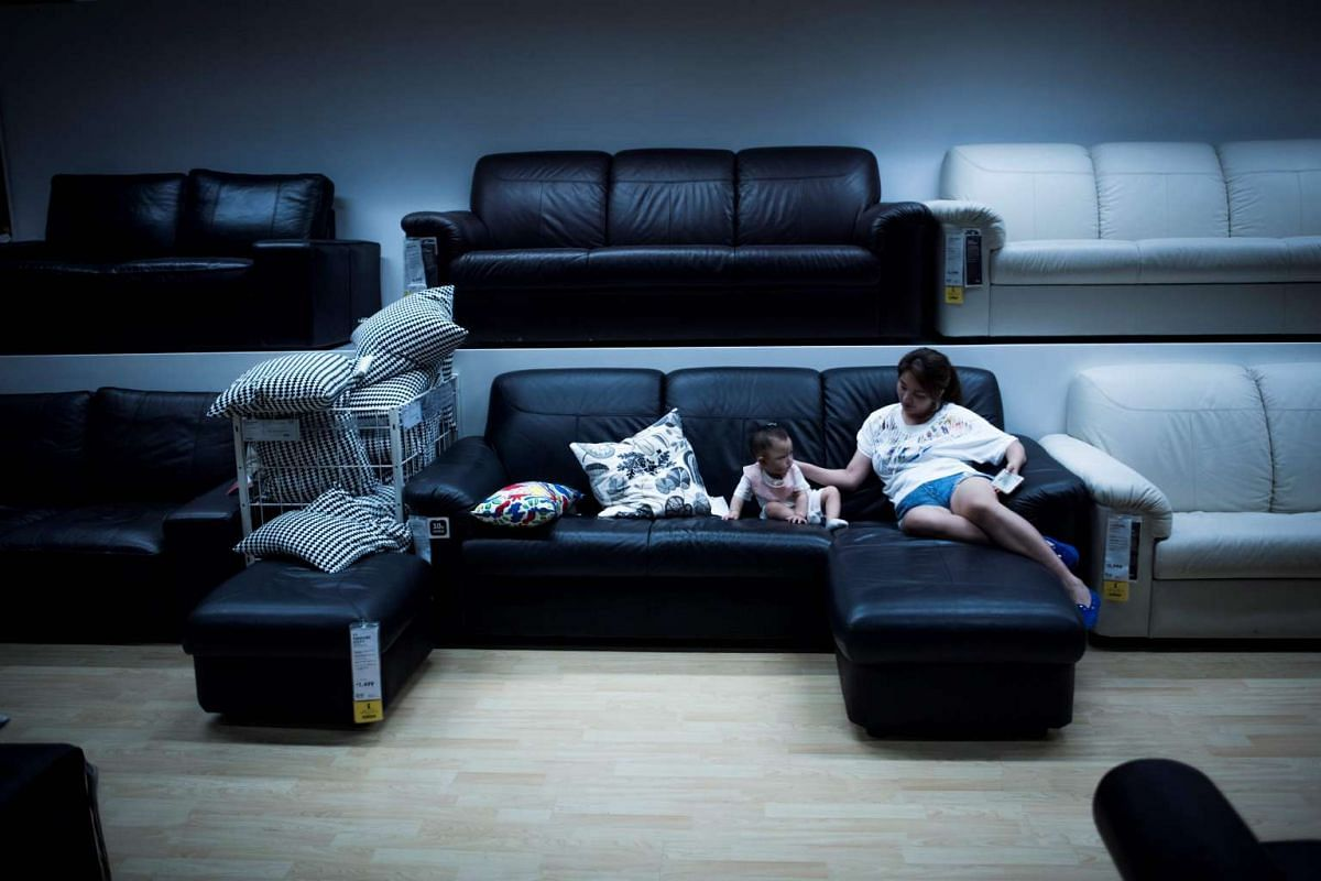 A mother and her child relaxing on a sofa in an Ikea store in downtown Shanghai to escape the summer heat on July 5, 2017.