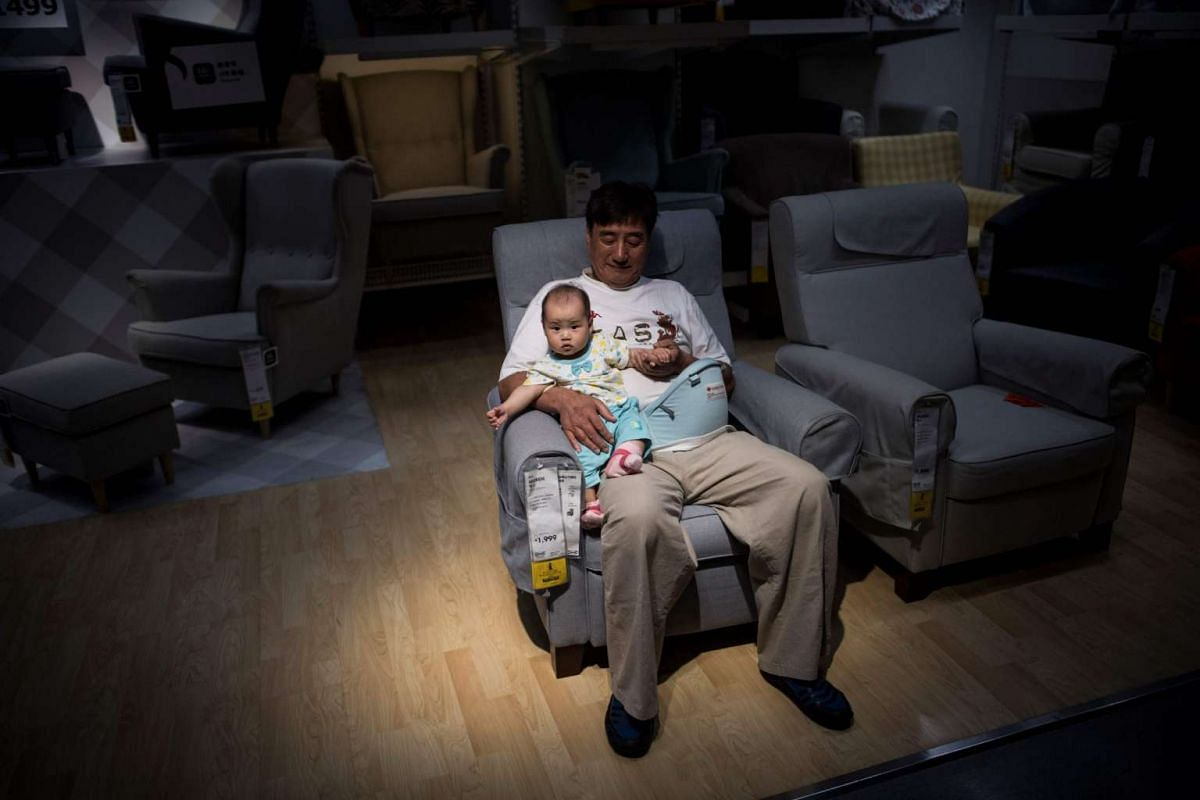 A man and a child escaping the summer heat on a sofa in an Ikea store in downtown Shanghai on July 5, 2017.