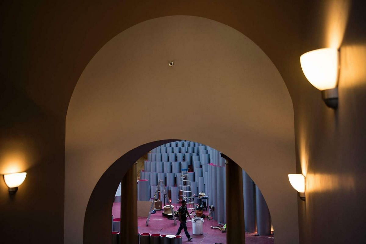 A worker walks past Studio Gang's Hive, made of over 2,700 wound paper tubes, in the Great Hall of the National Building Museum on July 3, 2017 in Washington, DC.