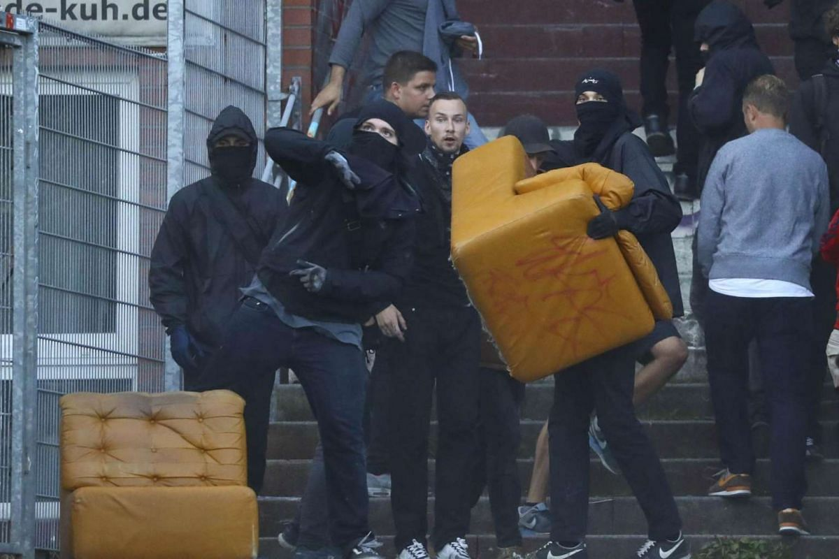 Anti-G-20 protesters throw items towards German riot police officers during clashes in Hamburg , Germany, on July 6, 2017.