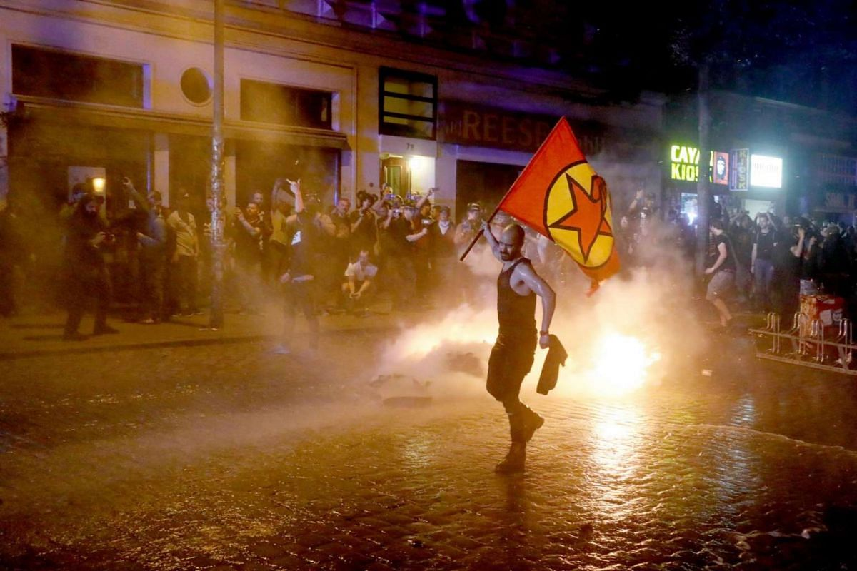 A protester waves a flag next to a fire on street near 'Rote Flora' building in 'Schanzenviertel' quarter ahead of the G-20 summit in Hamburg, Germany, on July 6 2017.