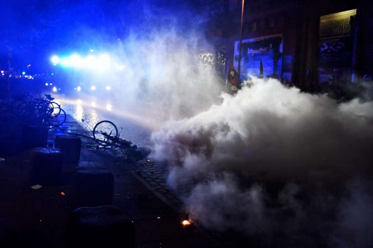 """Riot police use water cannon to put of burning bins after the """"Welcome to Hell"""" rally against the G-20 summit in Hamburg, northern Germany, on July 6, 2017."""