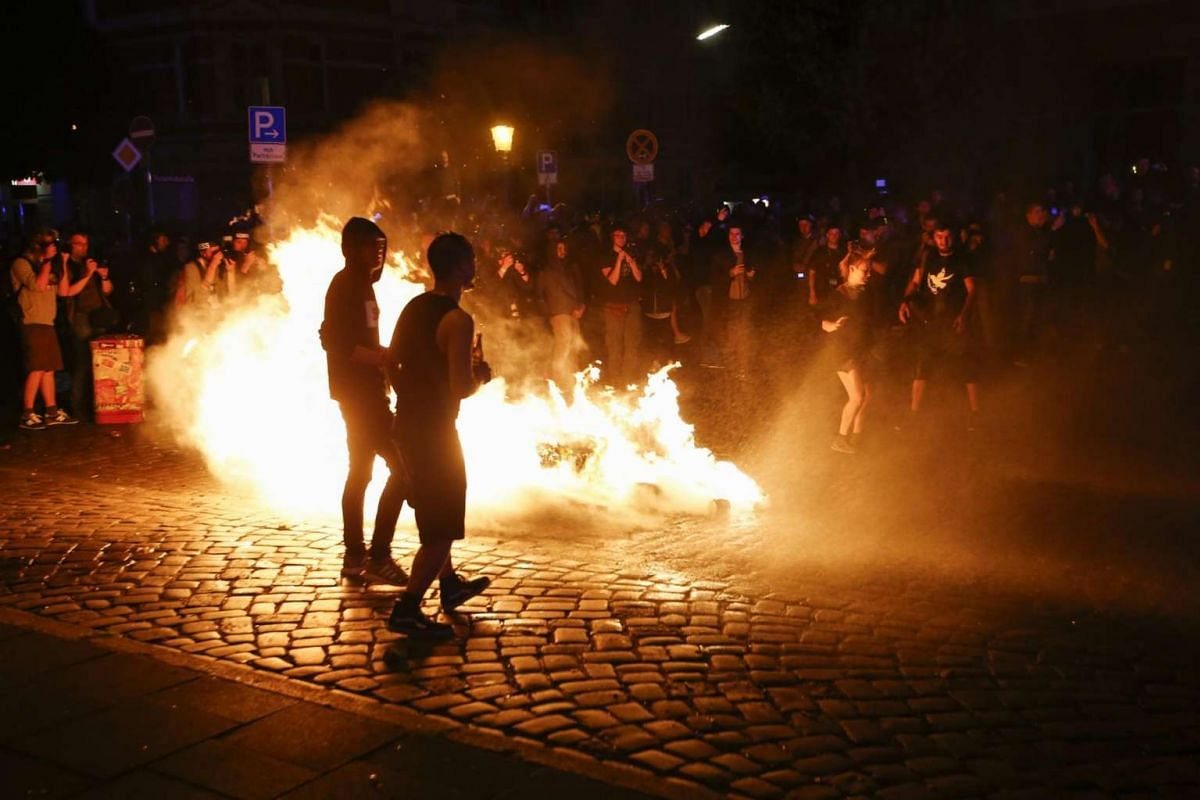 Protesters stand near a burning barricade during the demonstration during the G-20 summit in Hamburg, Germany, on July 6, 2017.