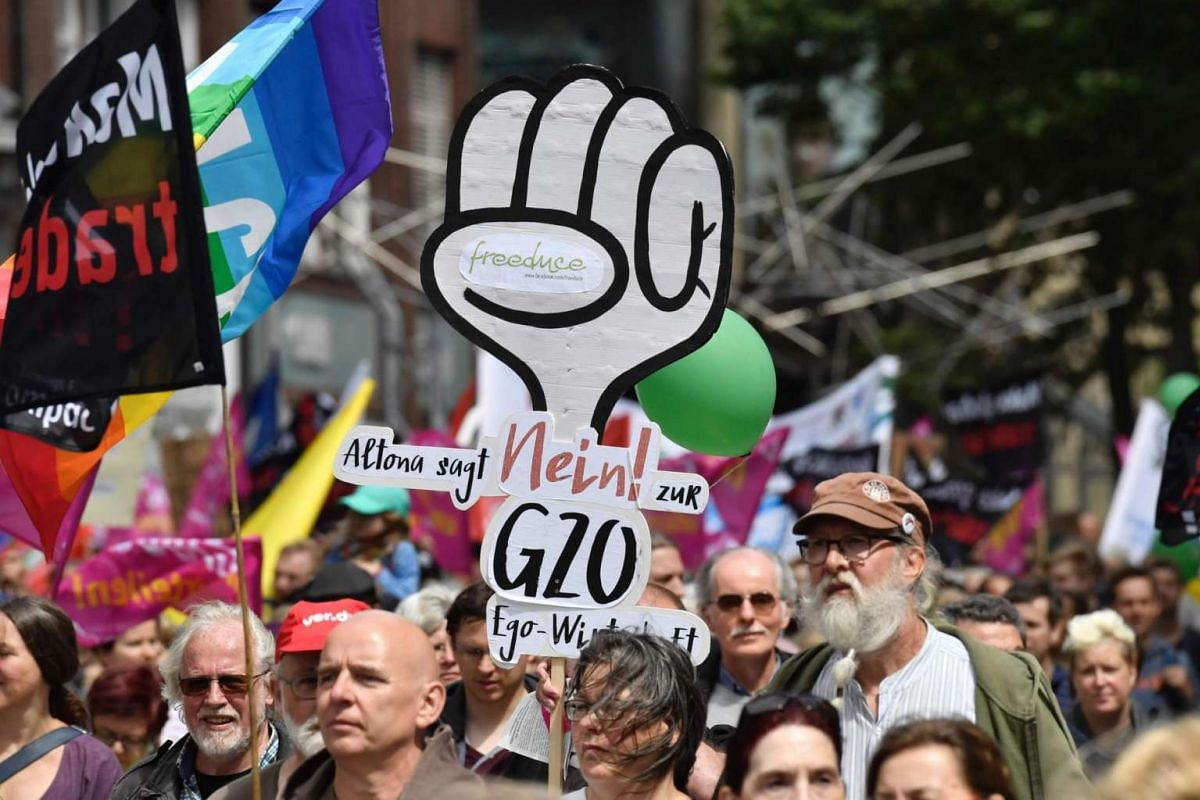 """Demonstrators display a placard that reads: """"(the Hamburg area of) Altona says no the the G20"""" during a demonstration called by several NGOs ahead of the G-20 summit in Hamburg, on July 2, 2017."""
