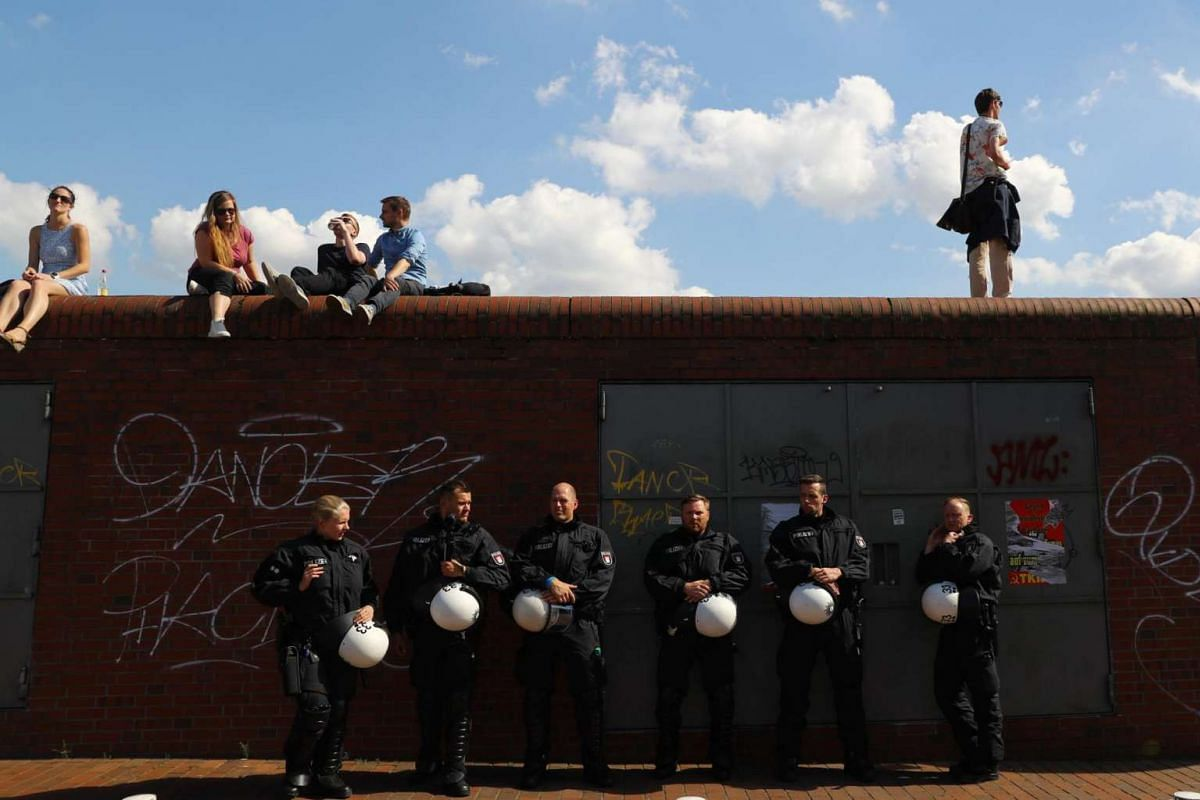 Protesters and German police officers wait for the start of the demonstration during the G-20 summit in Hamburg, Germany, on July 6, 2017.
