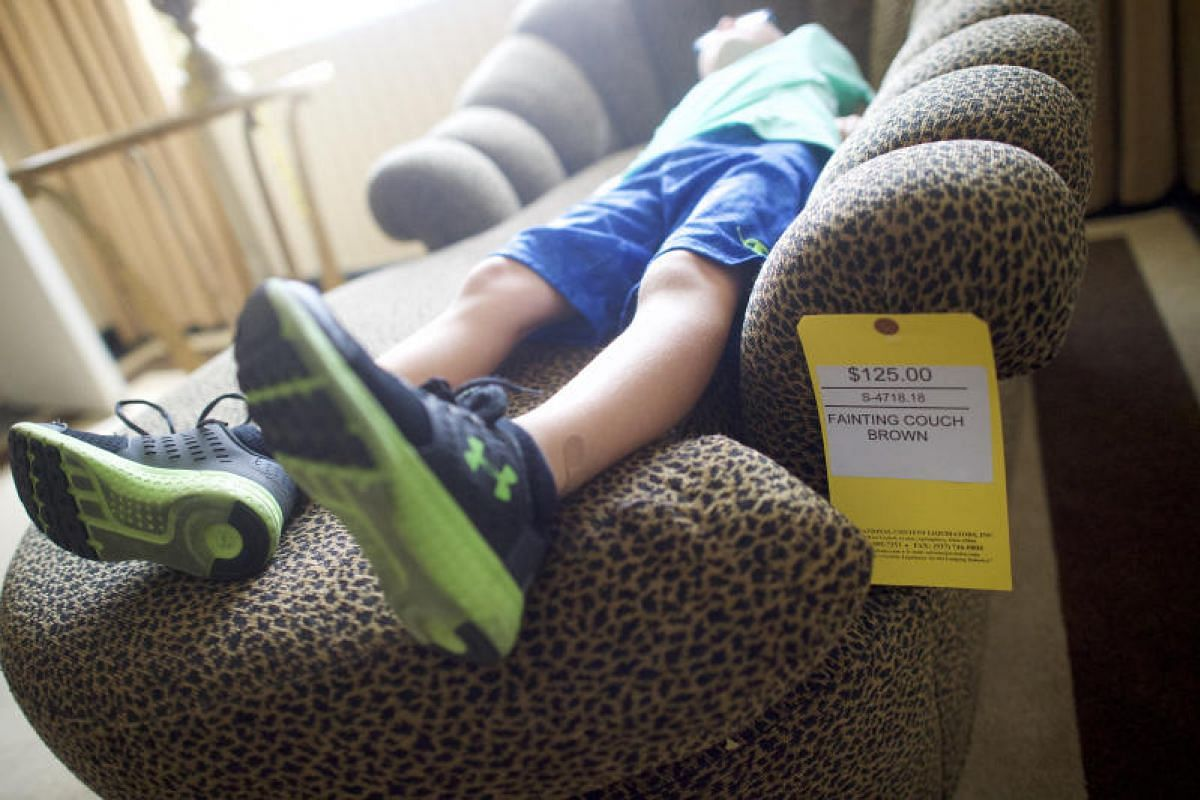 "Gavin Aloi, six, lying on a ""fainting couch"" during the liquidation sale of the former Trump Taj Mahal casino in Atlantic City, New Jersey, on July 6, 2017."