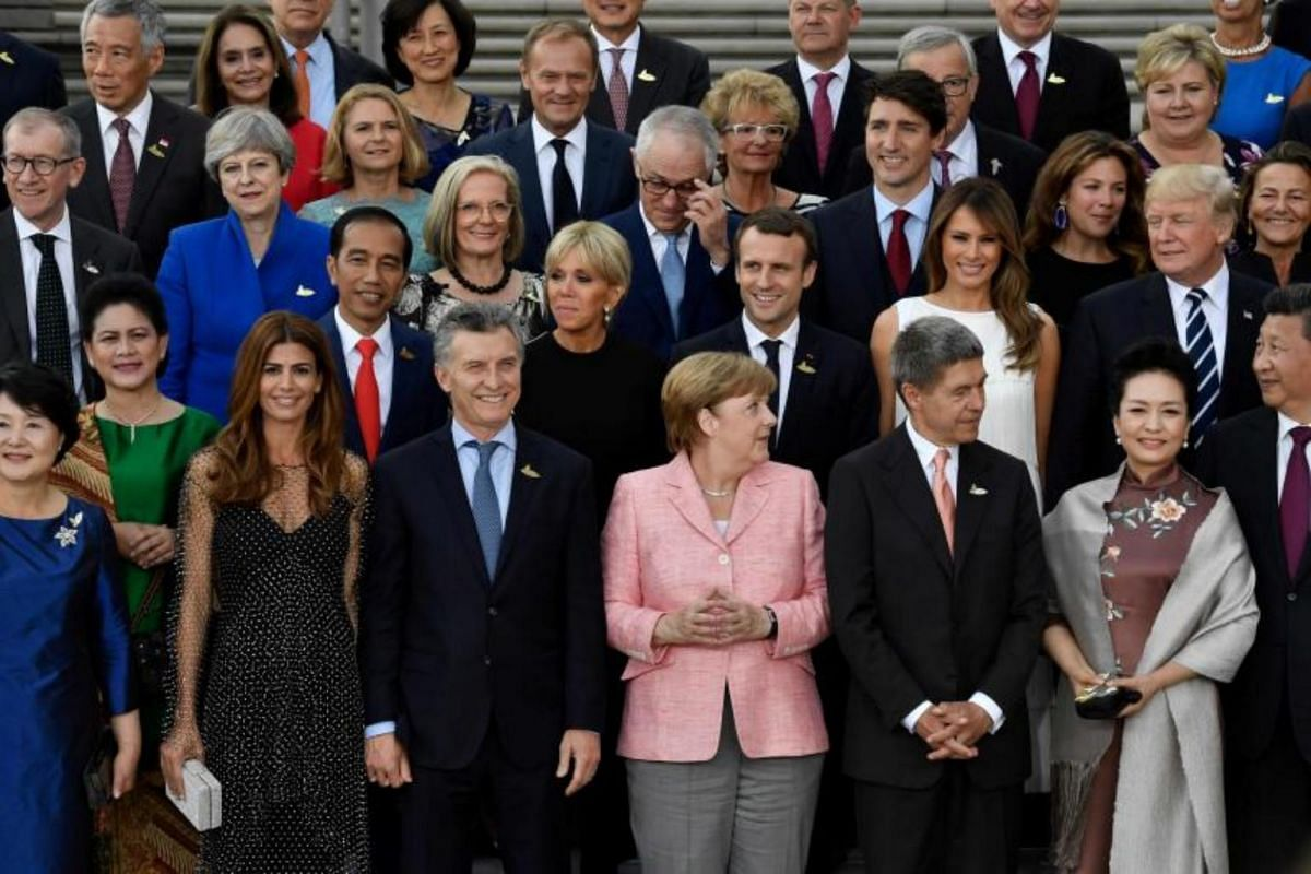 German Chancellor Angela Merkel (centre) and her husband Joachim Sauer (third, right) pose with other participants of the the G-20 Summit and their spouses for a family photo prior to a concert at the Elbphilharmonie concert hall during the G20 Summi