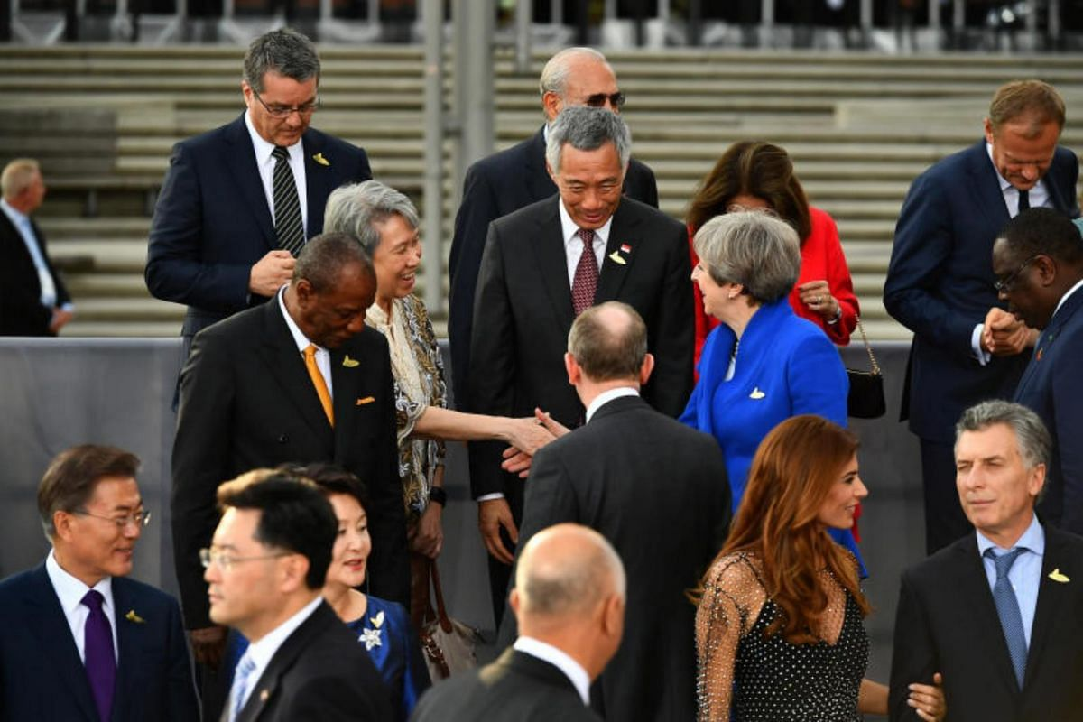 Ho Ching (left), the wife of Singapore Prime Minister Lee Hsien Loong, shakes hands with Prime Minister of the United Kingdom Theresa May before the family photo of G-20 participants and their spouses at the Elbphilharmonie in Hamburg, on July 7, 201