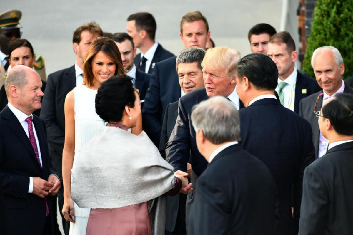 US President Donald Trump greeting Peng Liyuan (bottom, left), China's first lady, before the family photo of G-20 participants and their spouses at the Elbphilharmonie in Hamburg, on July 7, 2017.