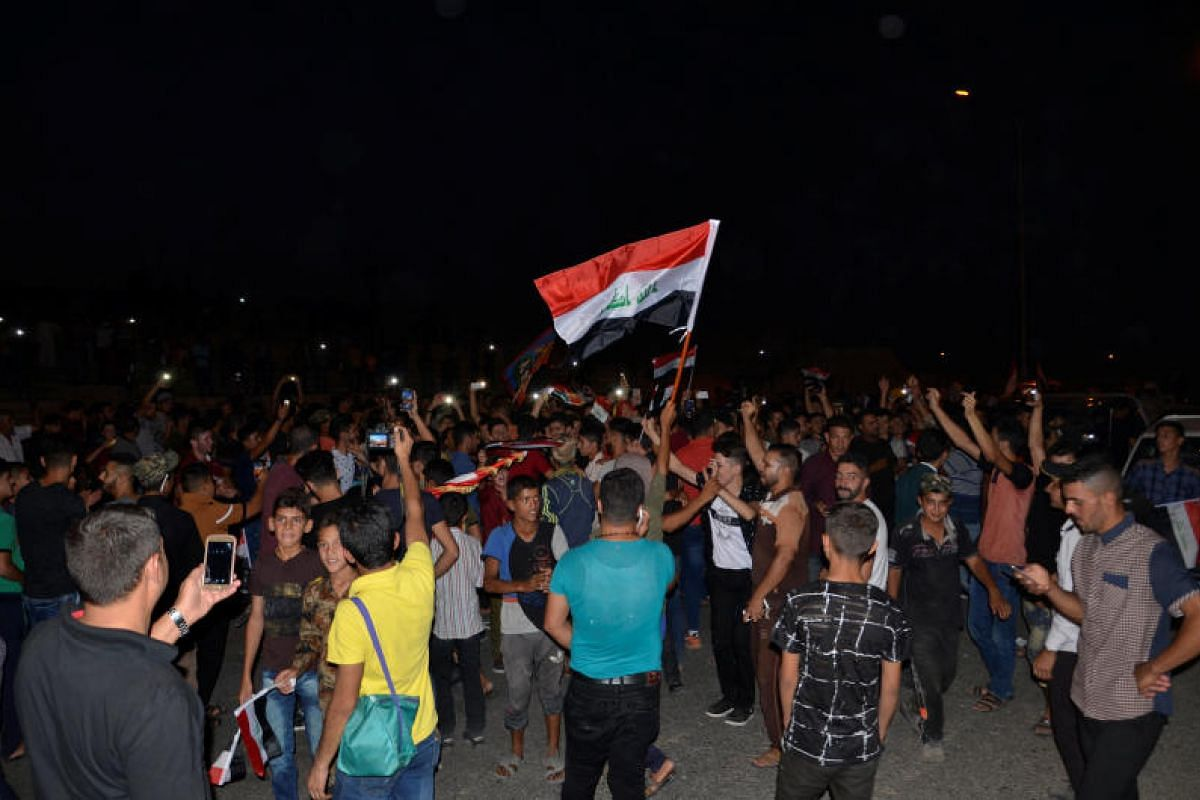 Iraqis celebrating the liberation of the embattled city of Mosul on Sunday (July 9), after it was seized by ISIS militants in June 2014.