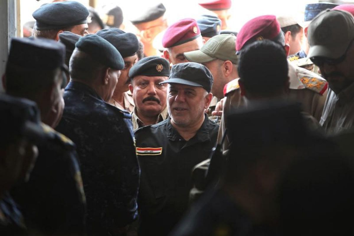 """Iraqi Prime Minister Haider al-Abadi (centre) congratulating military commanders in the al-Tayaran neighbourhood of Mosul on Sunday after the government announced the """"liberation"""" of the city from ISIS."""