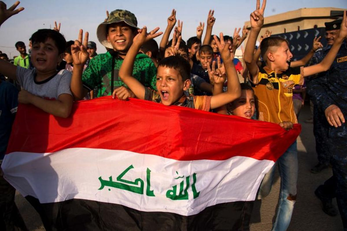 Excited children with Iraq's national flag cheer as they join government forces in celebrating the liberation of the Old City of Mosul.