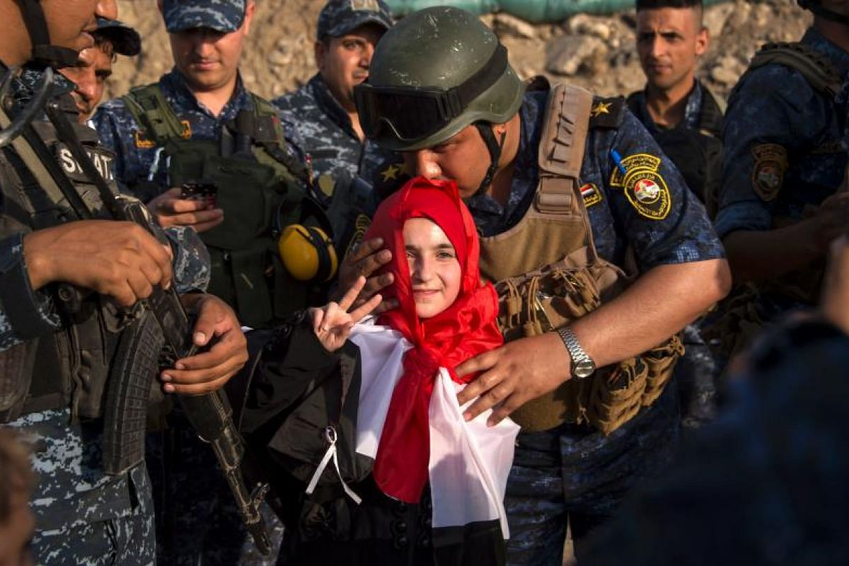 An Iraqi girl getting a kiss from a member of the federal police as forces celebrate in the Old City of Mosul after dealing  the biggest defeat yet to ISIS.