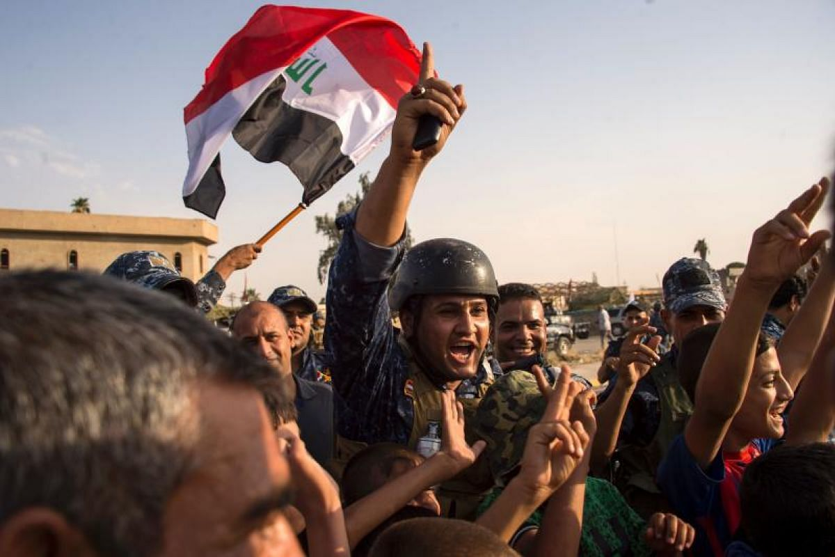 Iraqi federal police rejoicing in the defeat of ISIS militants in Mosul.