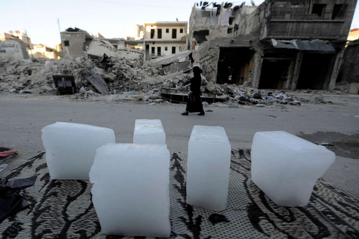 Pieces of ice are seen sale in al-Fardos district in Aleppo, Syria July 10, 2017.