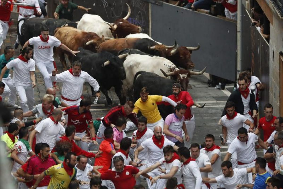Bulls from Fuente Ymbro bull ranch chase mozos, or runners, along Estafeta street during the fourth encierro, or bull run, of the San Fermin Festival 2017 in Pamplona, Spain, on July 10, 2017.