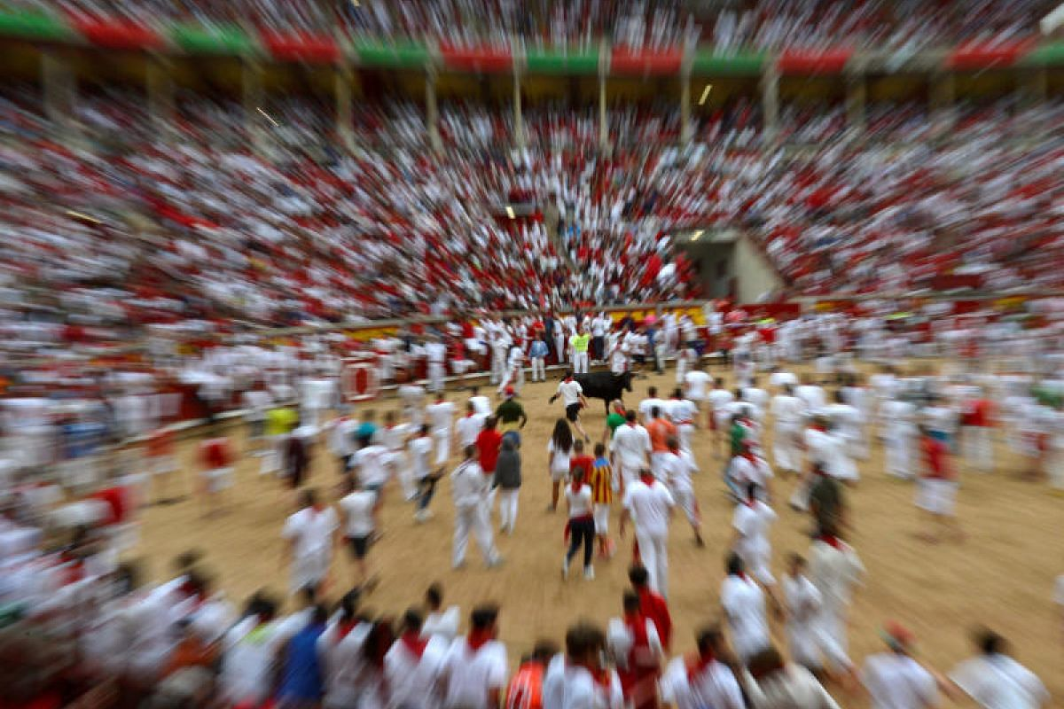 Revelers dodging a wild cow in the bull ring following the fourth running of the bulls at the San Fermin festival in Pamplona, northern Spain, on July 10, 2017.