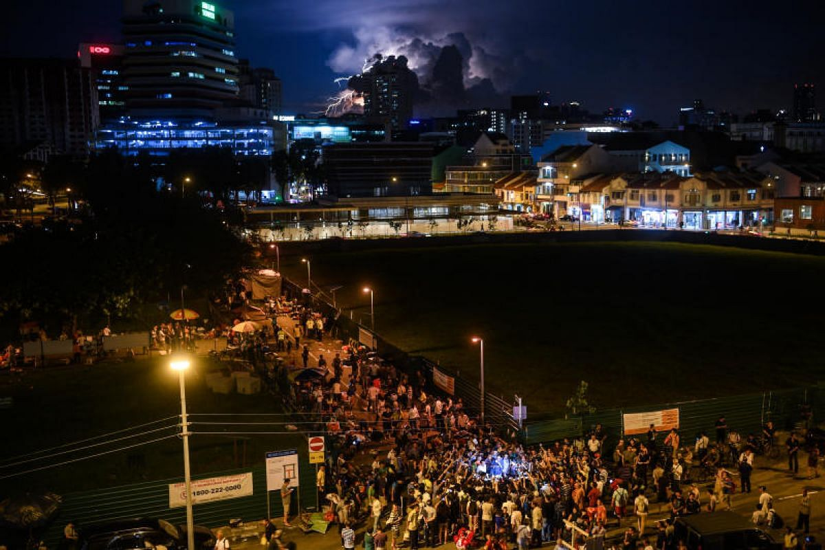 Lightning striking as a crowd gathers to hear the Save Sungei Road Market Group and the market's association give a statement at the end of its day of trade.