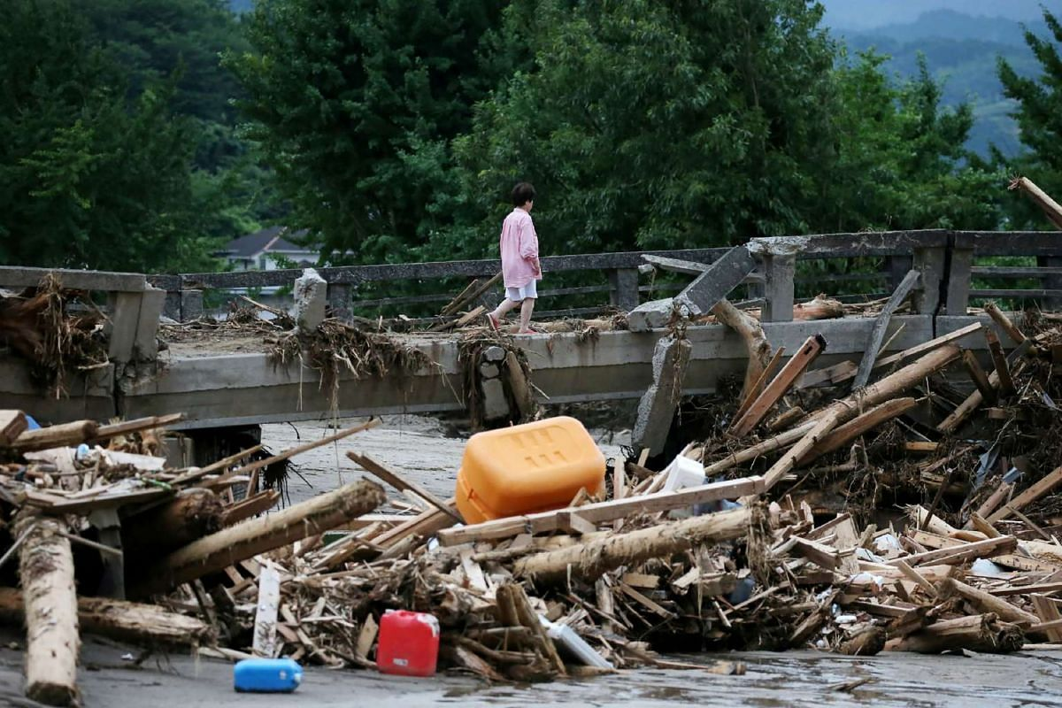 A resident walks across a damaged bridge in a flooded area in Asakura city, Fukuoka prefecture on July 11, 2017. The death toll from heavy rains and flooding in Japan's south has risen to 25, the government said on July 11, as rescue teams continued