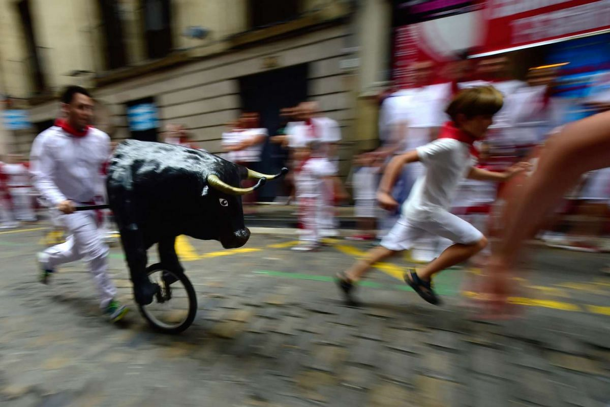 "Children run in the the ""Encierro Txiki"" (Small Bull Run) during the San Fermin Festival in Pamplona, northern Spain on July 10, 2017. The festival is a symbol of Spanish culture that attracts thousands of tourists to watch the bull runs despite heav"