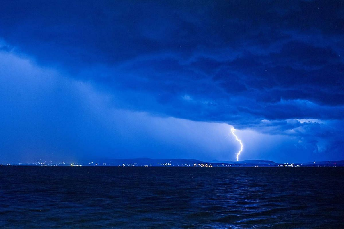 Lightning strikes from dark clouds during a storm near Revfulop, as seen from Balatonlelle, Hungary, late July 11, 2017