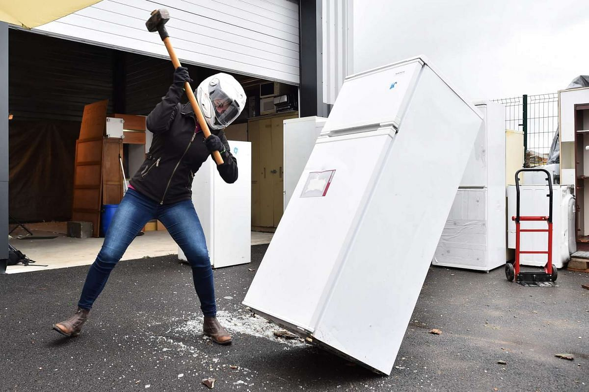 A person destroys a refridgerator with a sledgehammer in Noyal-Chatillon-sur-Seiches, western France. Spraying plates, smashing a fridge or taking a baseball bat to a microwave or golf club, and feel more zen, is a move of a sophrologist who organize
