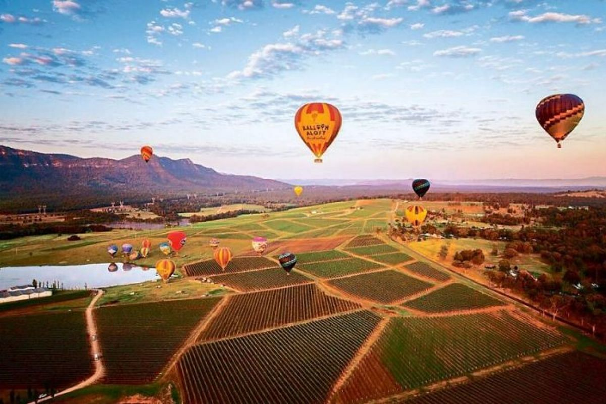 An epic way to see the sunrise is a hot-air balloon ride above Hunter Valley.