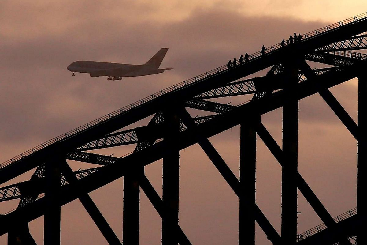 A plane prepares to land at Sydney International Airport behind climbers on the Sydney Harbour Bridge at sunset in Australia, July 12, 2017.