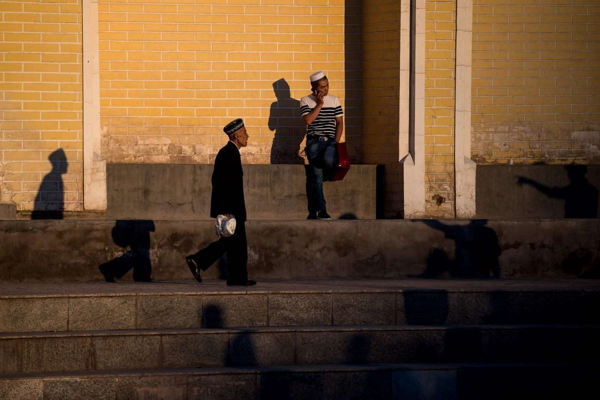 Muslim men outside the Id Kah Mosque as they prepare to attend the morning prayer on Eid al-Fitr in the old town of Kashgar in China's Xinjiang Uighur Autonomous Region.