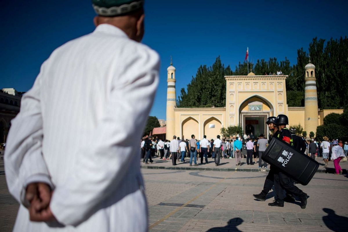 Muslim men arriving at the Id Kah Mosque for the morning prayer on Eid al-Fitr in the old town of Kashgar in China's Xinjiang Uighur Autonomous Region.