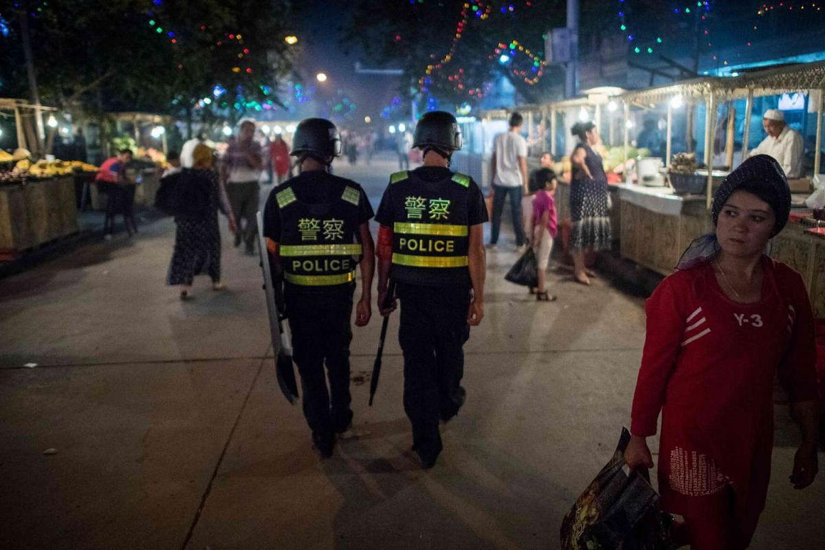 Police patrolling in a night food market near the Id Kah Mosque in Kashgar in China's Xinjiang Uighur Autonomous Region, a day before the Eid al-Fitr holiday.