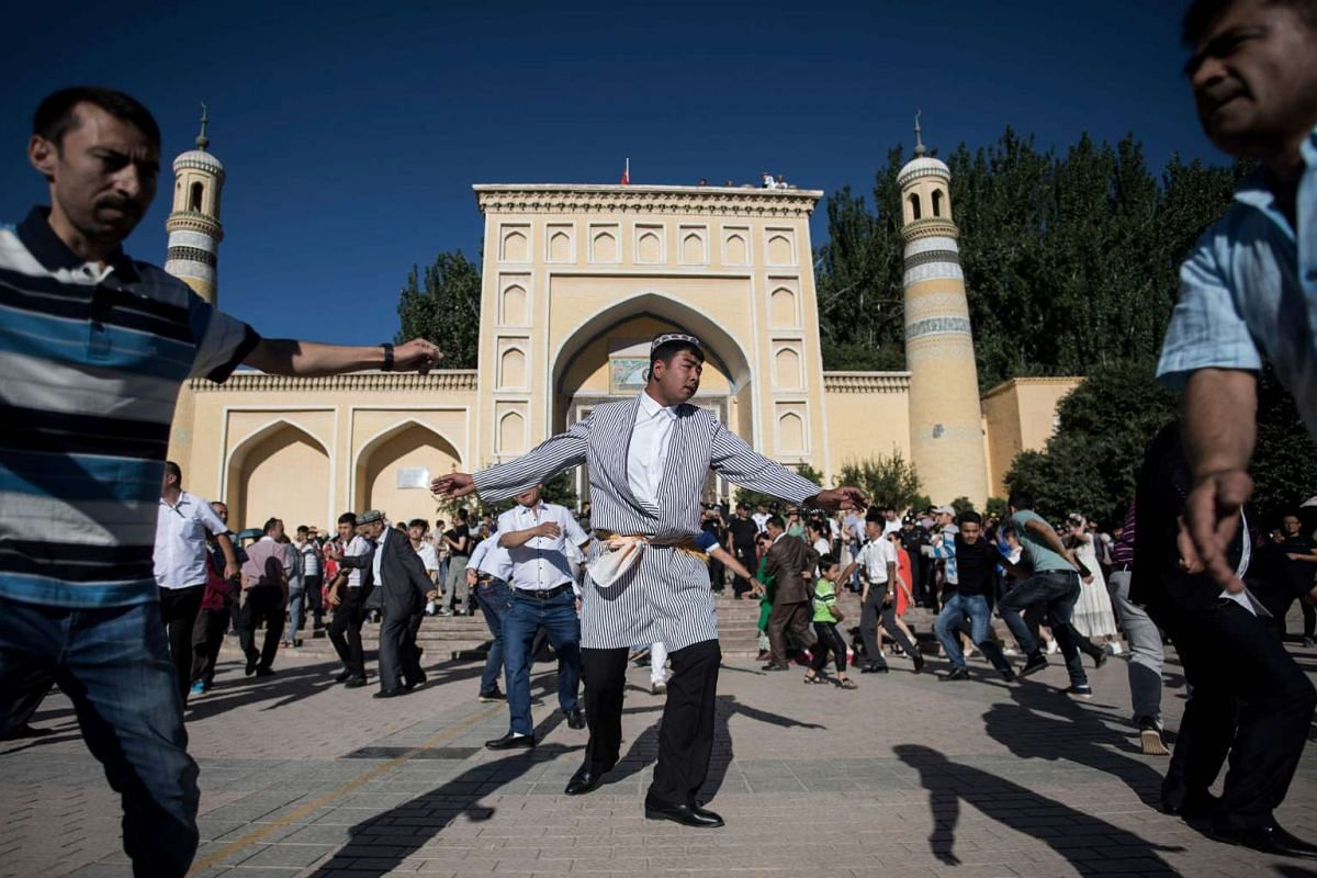 Men dancing in front of the Id Kah Mosque after the morning prayer on Eid al-Fitr in the old town of Kashgar in China's Xinjiang Uighur Autonomous Region.