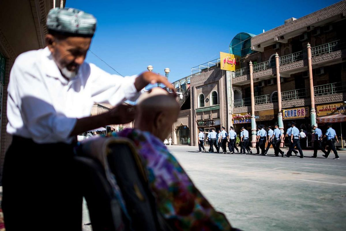Police walking past a barber near the Id Kah Mosque in the old town of Kashgar in China's Xinjiang Uighur Autonomous Region, after the morning prayer on Eid al-Fitr.