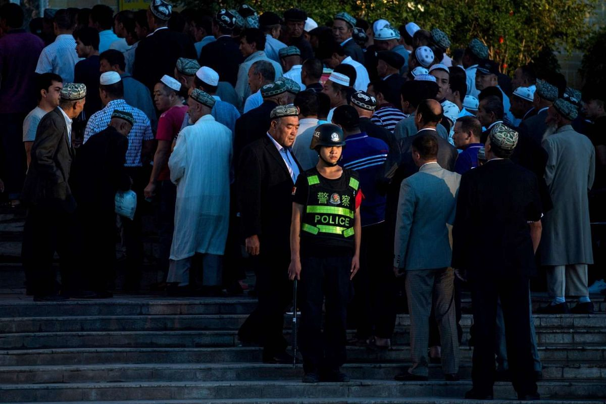 A policeman standing guard as Muslims arrive for the Eid al-Fitr morning prayer at the Id Kah Mosque in Kashgar in China's Xinjiang Uighur Autonomous Region.