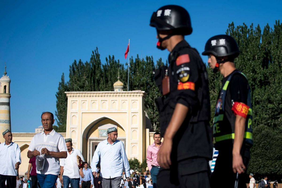 Police patrolling as Muslims leave the Id Kah Mosque after the morning prayer on Eid al-Fitr in the old town of Kashgar in China's Xinjiang Uighur Autonomous Region.