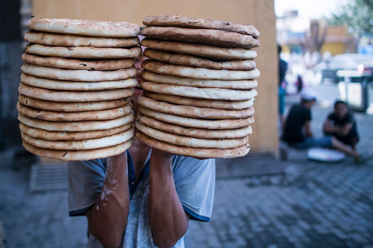 A man carrying breads to a shop in Yarkand, in China's Xinjiang Uighur Autonomus Region.