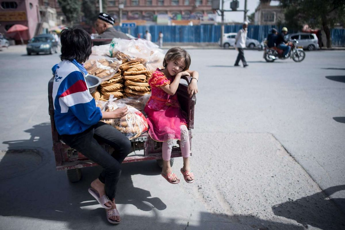 Children riding on the back of a tricycle of a Muslim sweet vendor in Yarkand, in China's Xinjiang Uighur Autonomus Region.